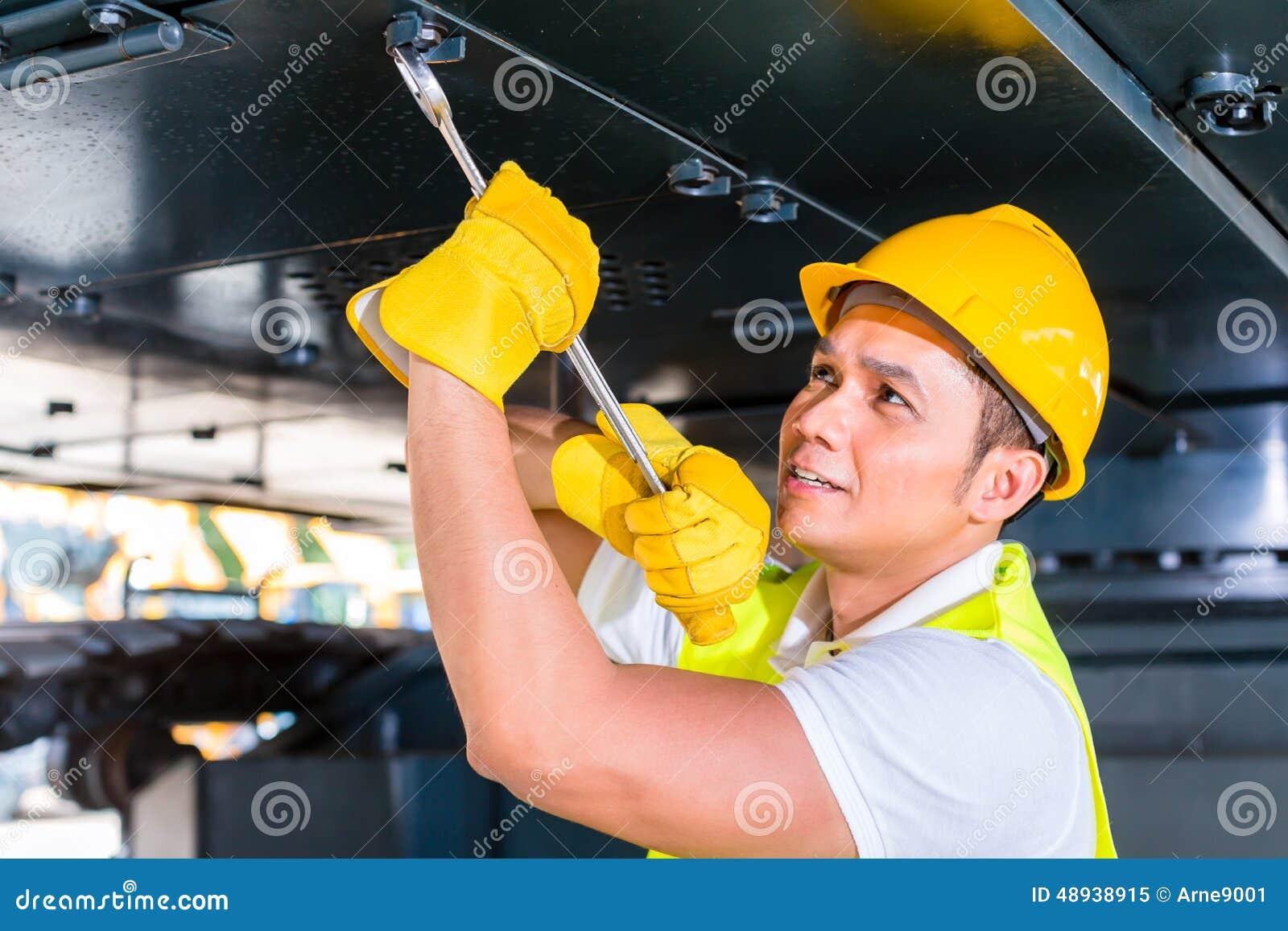 修理建筑车的亚裔技工