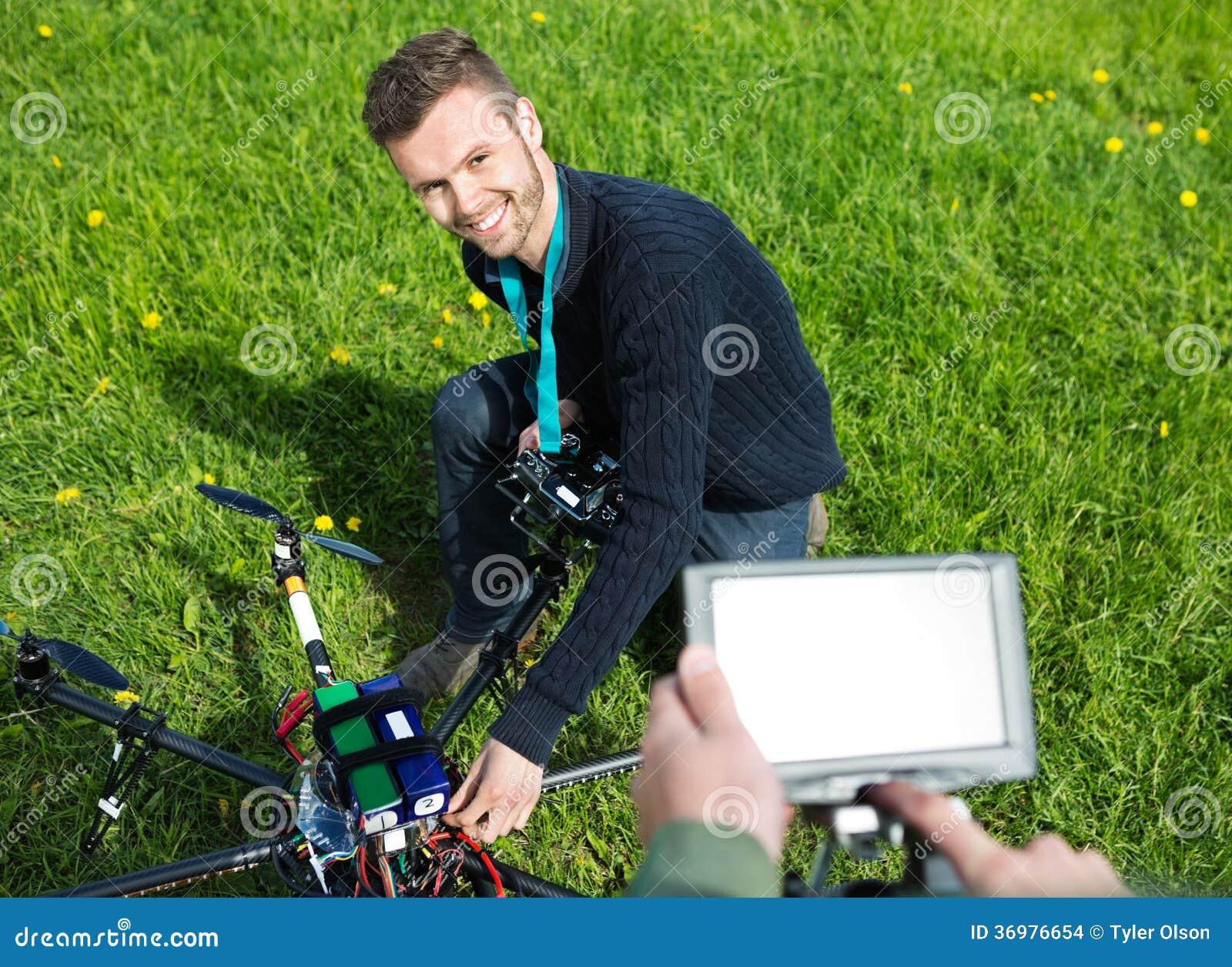 修理UAV直升机的工程师在公园