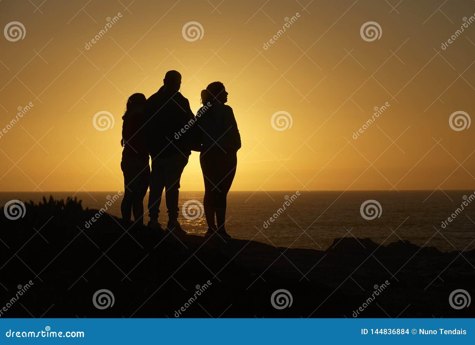 俯视海洋的家庭剪影