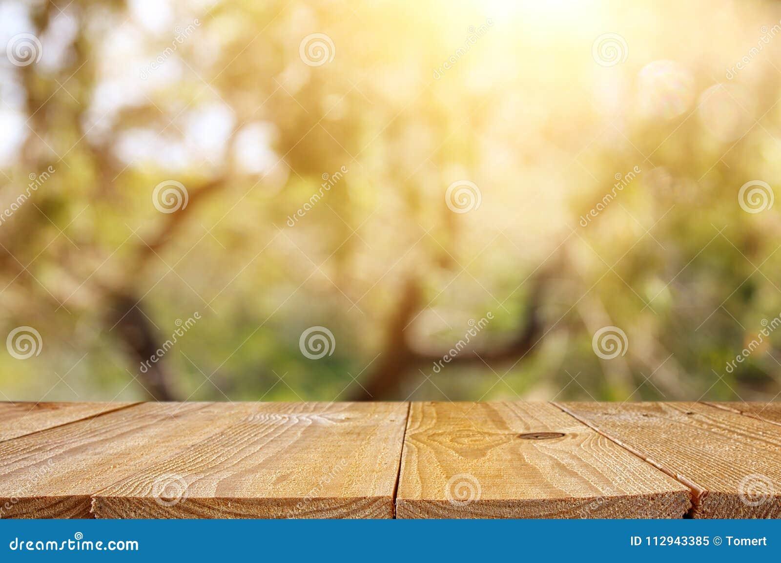 倒空在绿色春天摘要bokeh背景前面的土气桌 产品显示和野餐概念