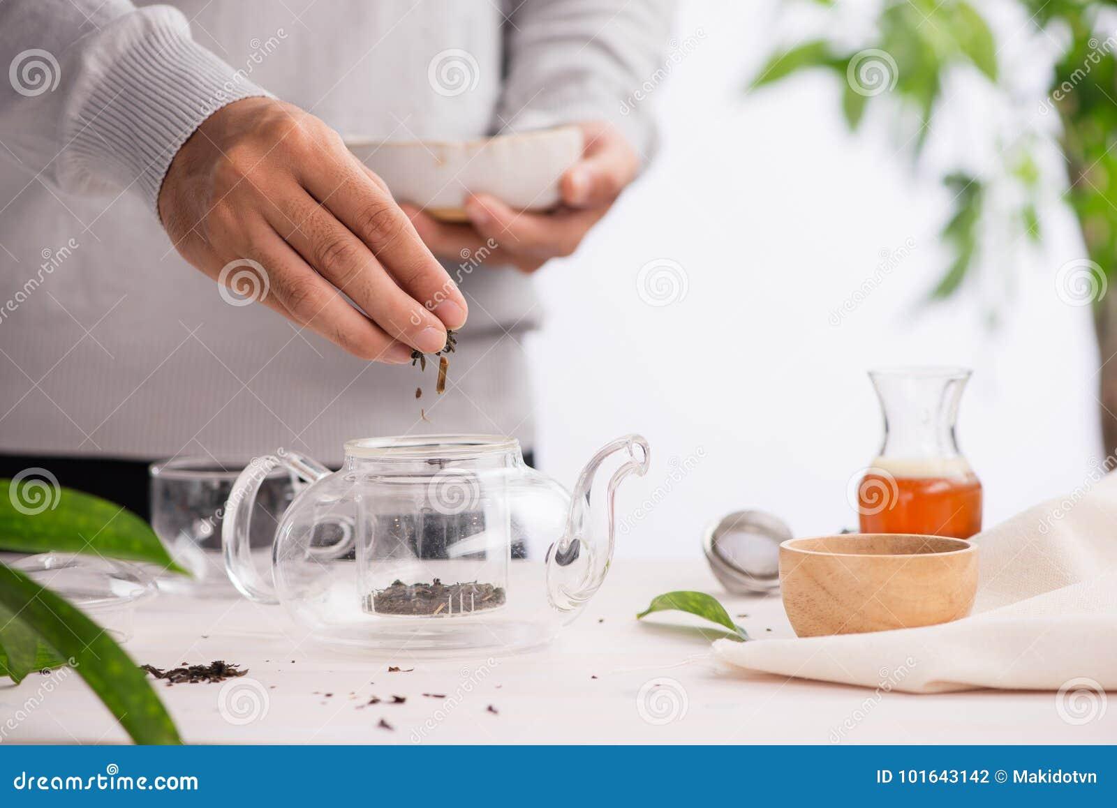 倾吐的健康茶 在一个玻璃茶壶的热的茶在一张木桌上