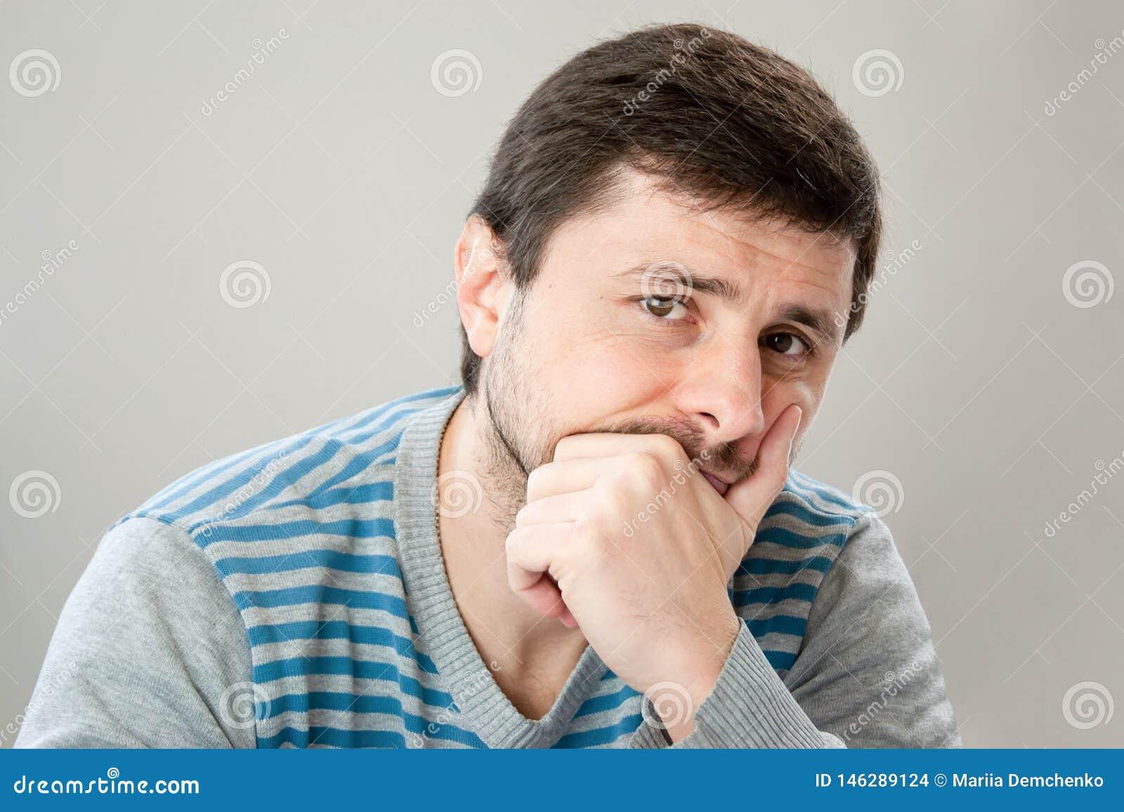 倾斜他的头的一件镶边毛线衣的体贴的英俊的有胡子的人反对他的看照相机的手