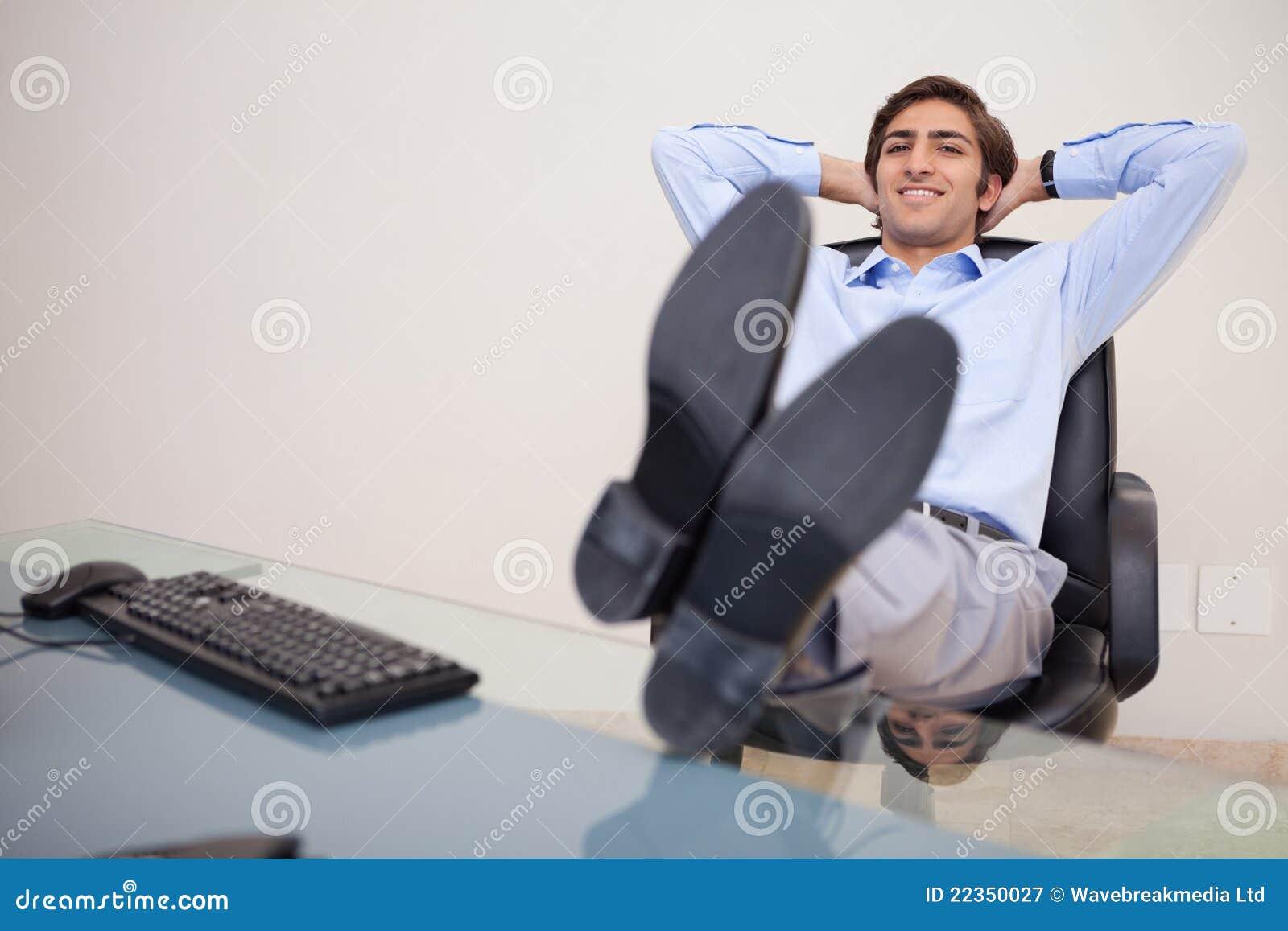 倾斜在他的椅子的微笑的生意人
