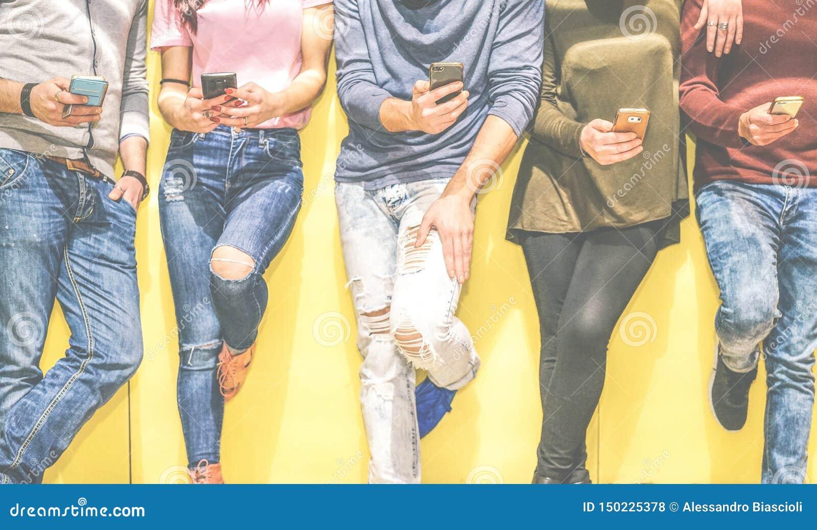 倾斜在墙壁的小组年轻朋友使用手机-连接在人脉的多种族人民用智能手机