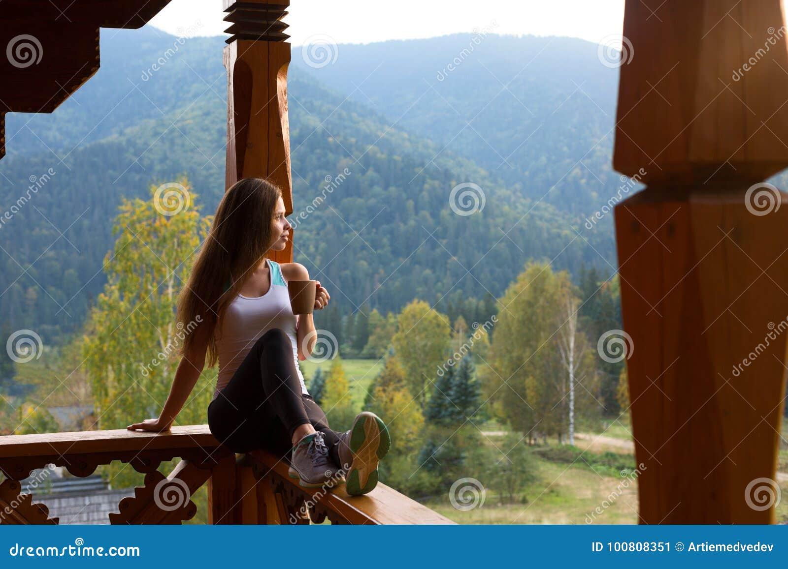 倾斜在木扶手栏杆的妇女和享用并且放松风景美丽的山 坐的大阳台的年轻女性