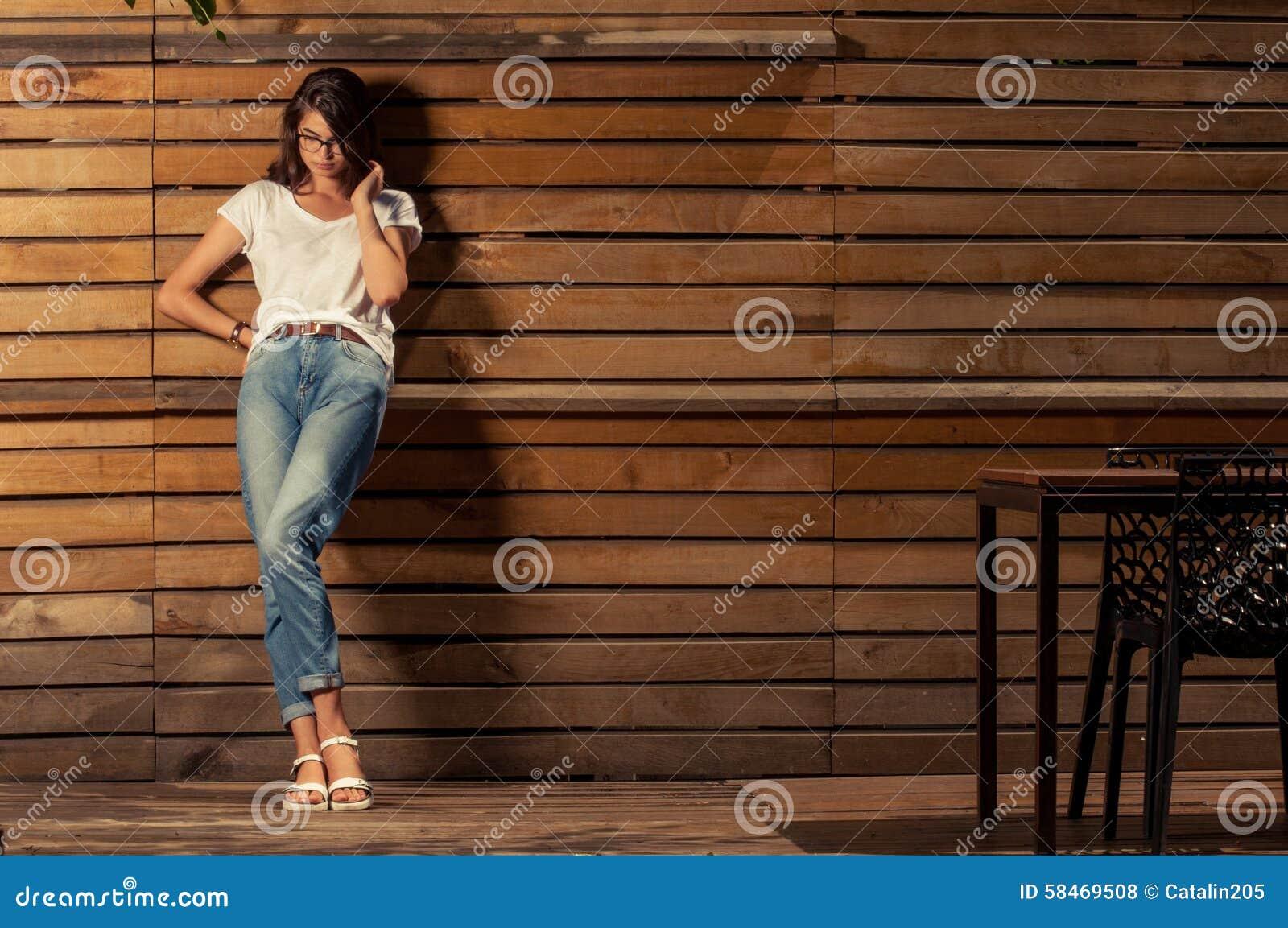 倾斜在木篱芭的美丽的行家妇女