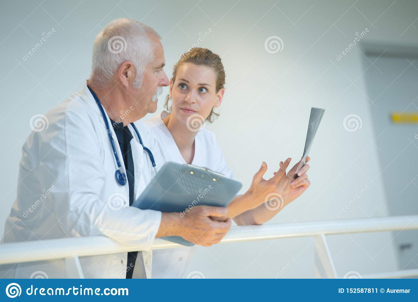 倾斜在楼梯栏杆的讨论的医护人员