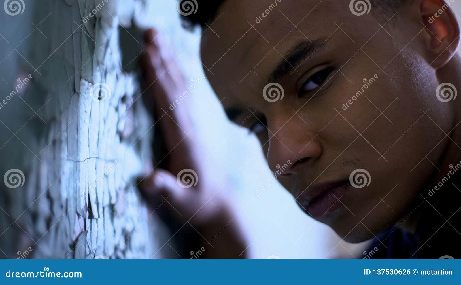 倾斜在片状墙壁、贫穷和生活困难,悲伤的美国黑人的男孩