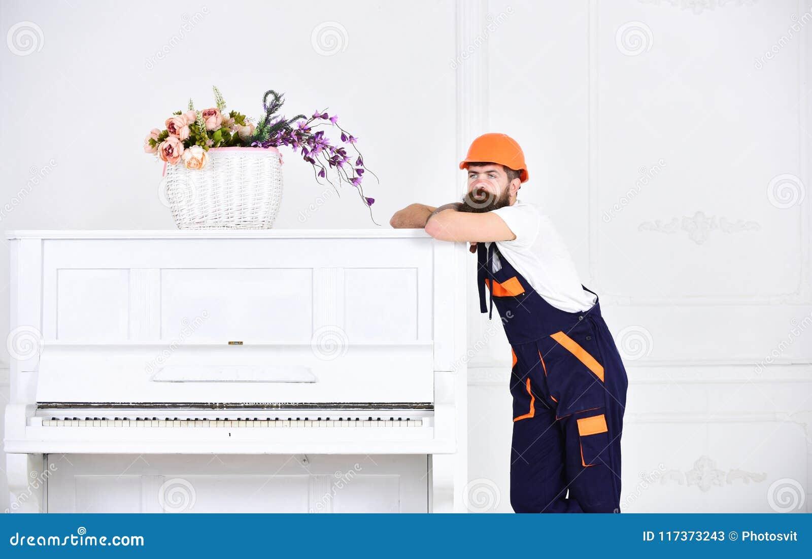 倾斜在葡萄酒白色钢琴上面的体贴的人与在白色背景隔绝的玻璃花瓶的 博若莱红葡萄酒