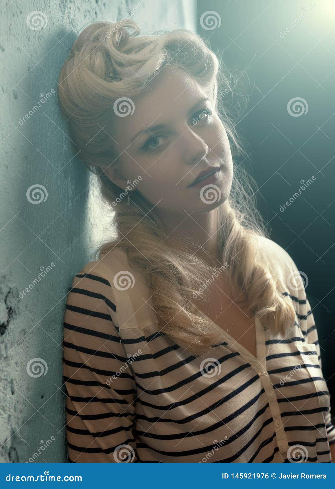 倾斜对墙壁的美丽的金发碧眼的女人照亮与聚光灯