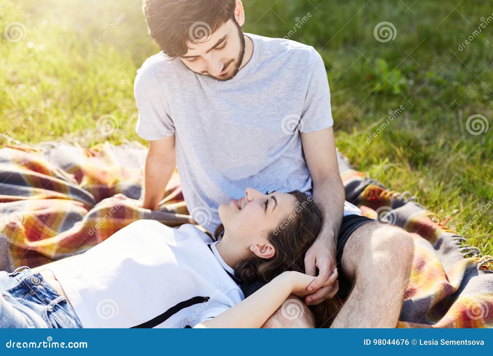 假日、假期、爱和友谊概念 在一起基于草甸绿草的爱的夫妇,看在e
