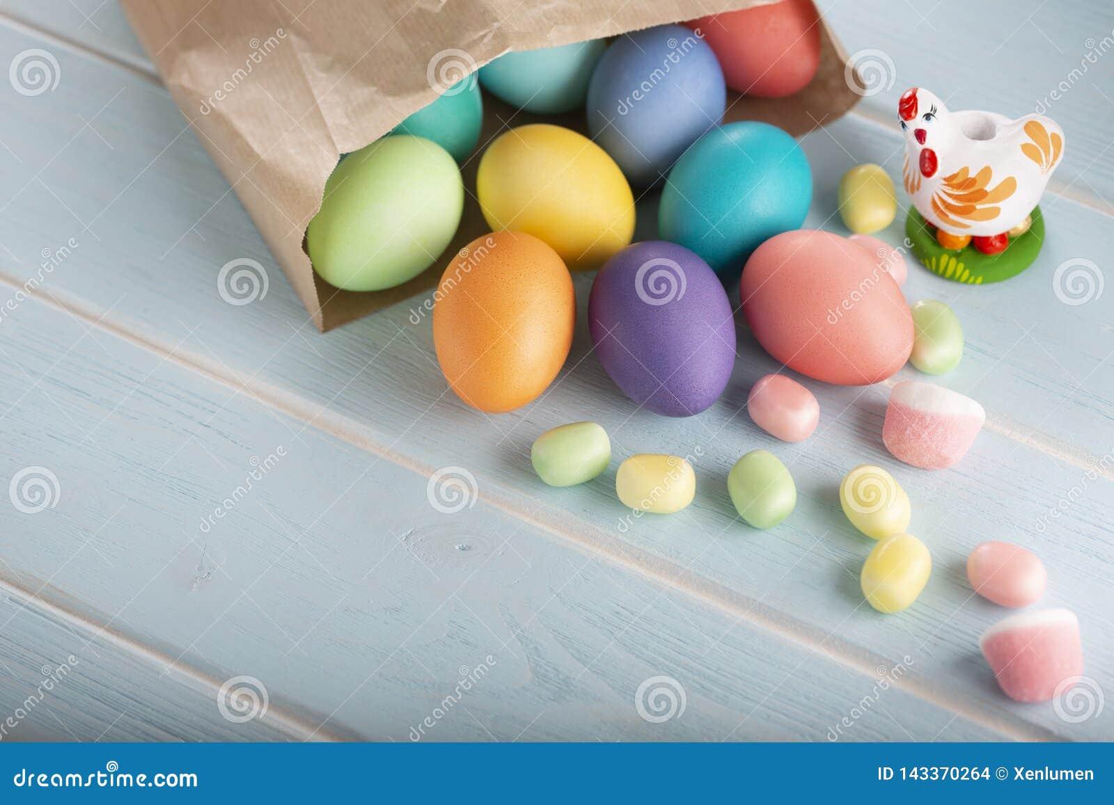 假日复活节五颜六色的鸡鸡蛋的混合在纸工艺袋子和甜点的