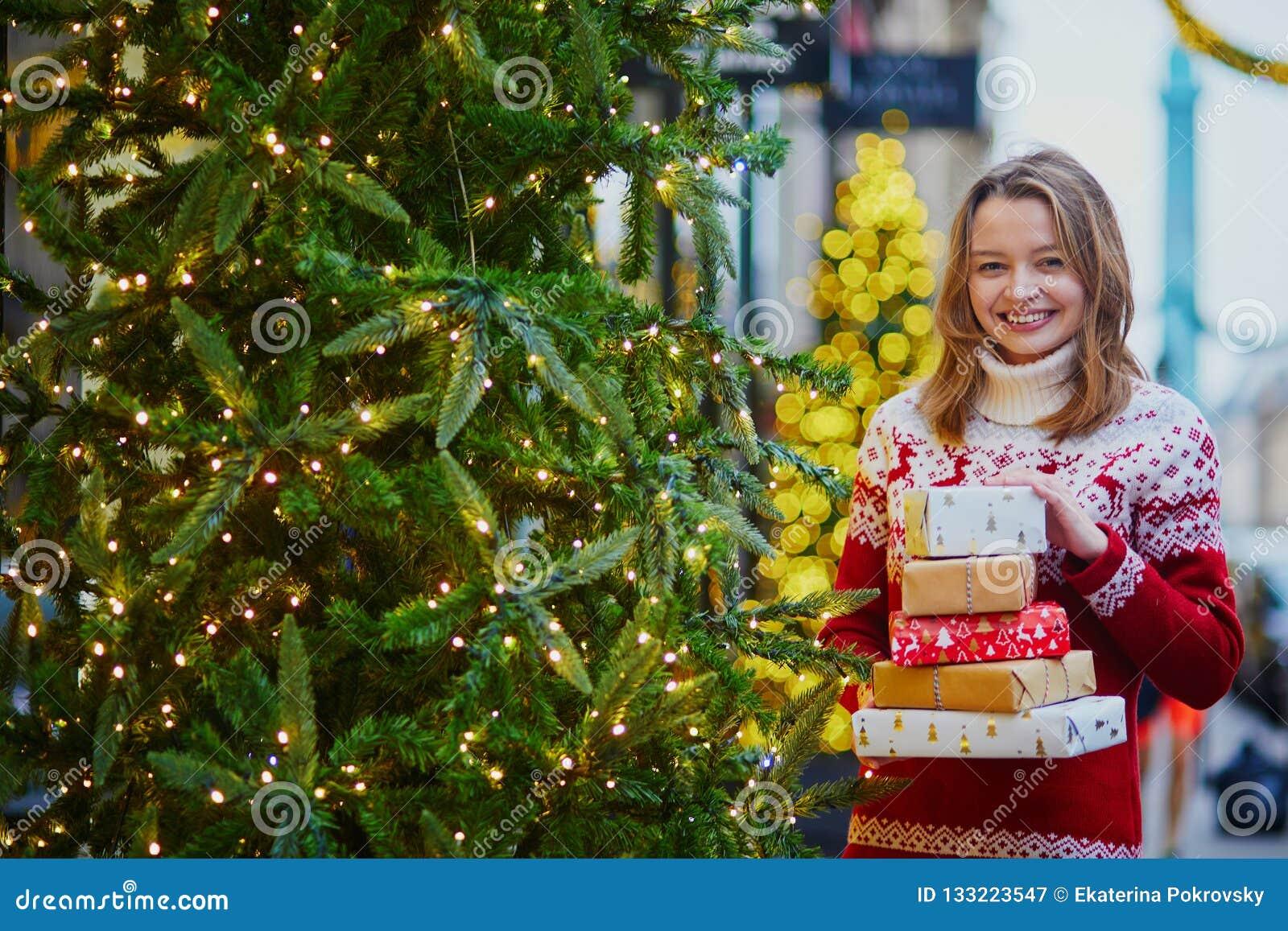 假日毛线衣的愉快的少女有堆的圣诞礼物