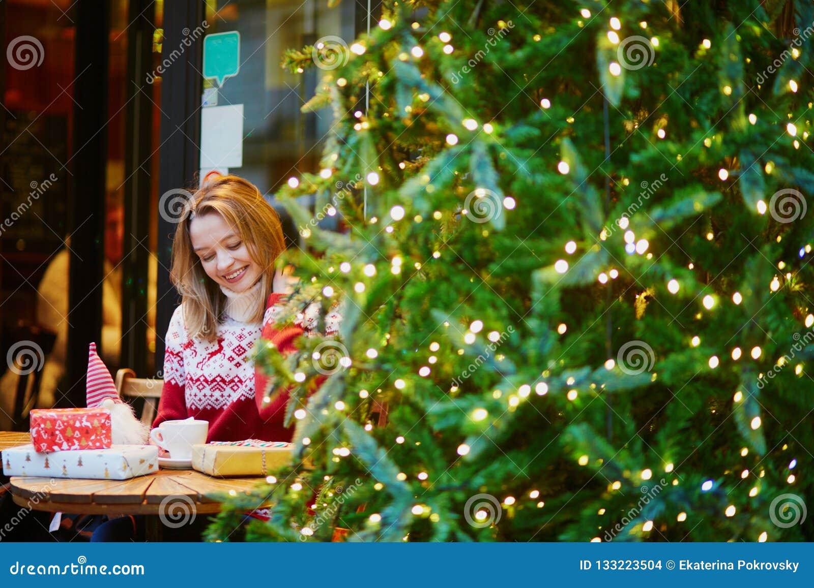 假日毛线衣饮用的咖啡或巧克力热饮的女孩在为圣诞节装饰的咖啡馆