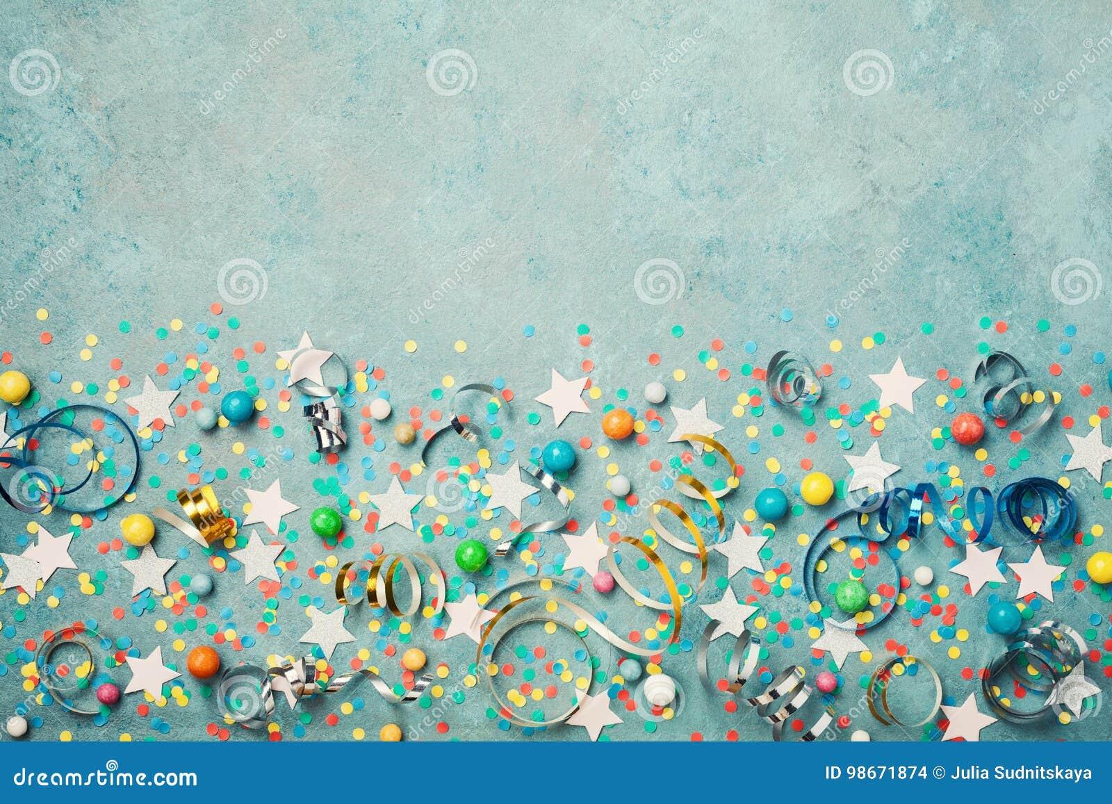 假日背景装饰了五颜六色的五彩纸屑、星、糖果和飘带在蓝色葡萄酒台式视图 平的位置 欢乐的边界