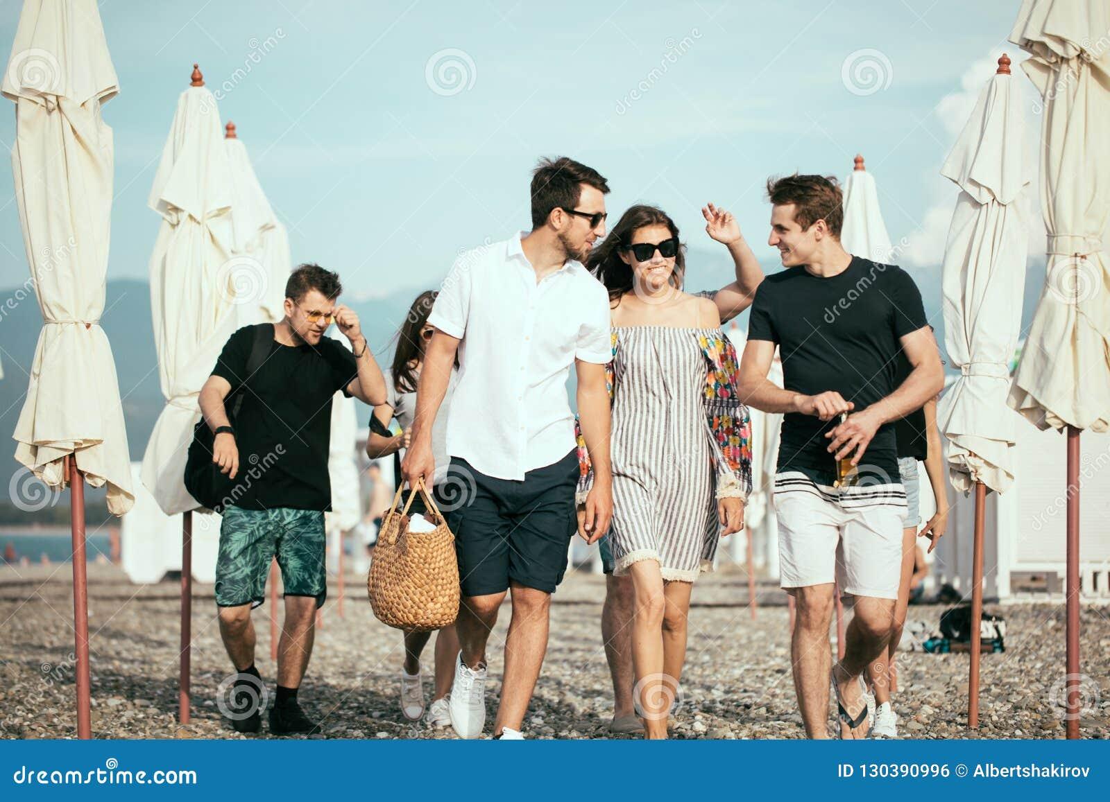 假日,假期 获得小组的朋友在海滩,走,饮料啤酒,微笑和拥抱的乐趣