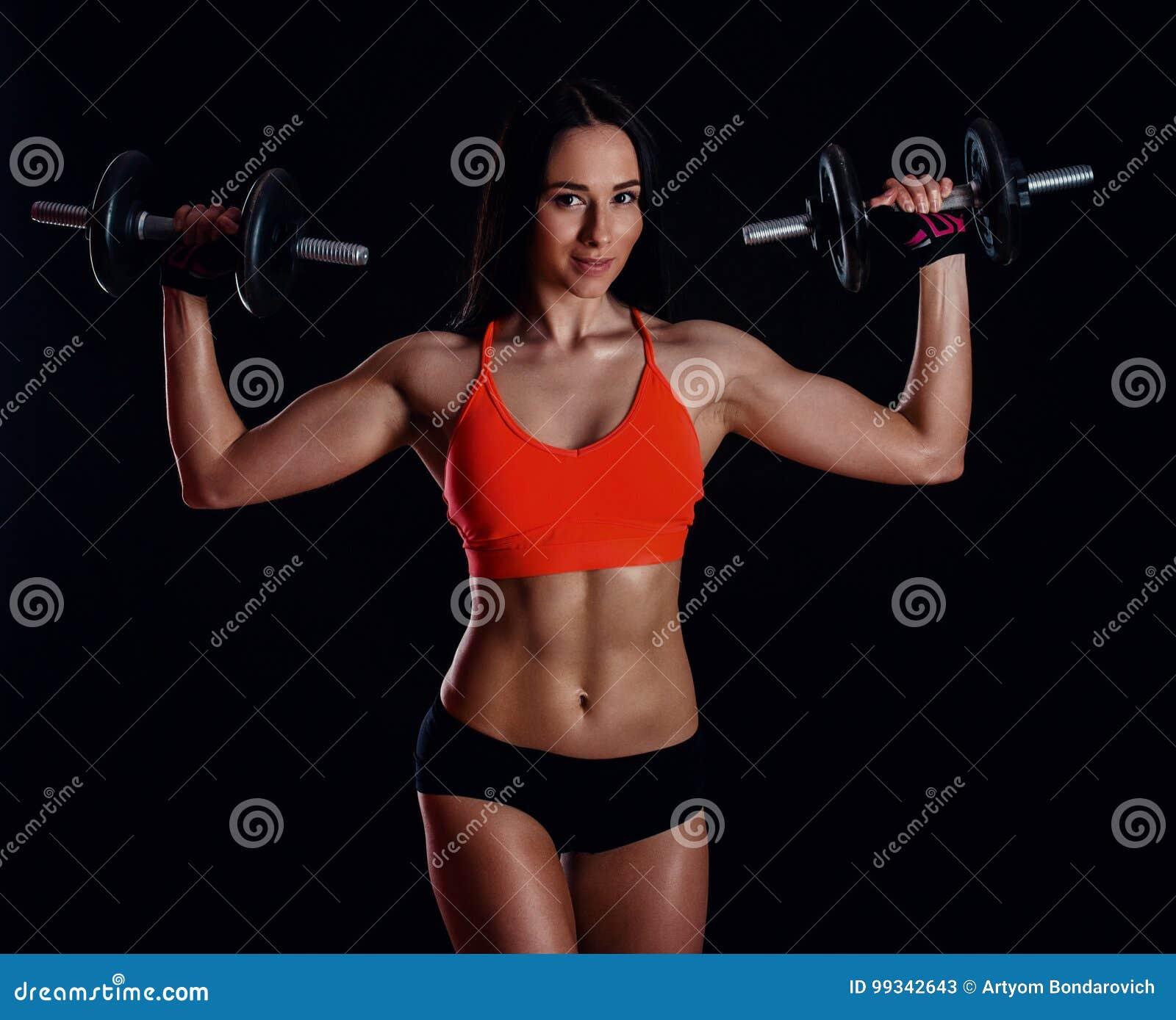 做与哑铃的好性感的女孩锻炼被隔绝在黑背景 运动少妇做与重量的健身锻炼
