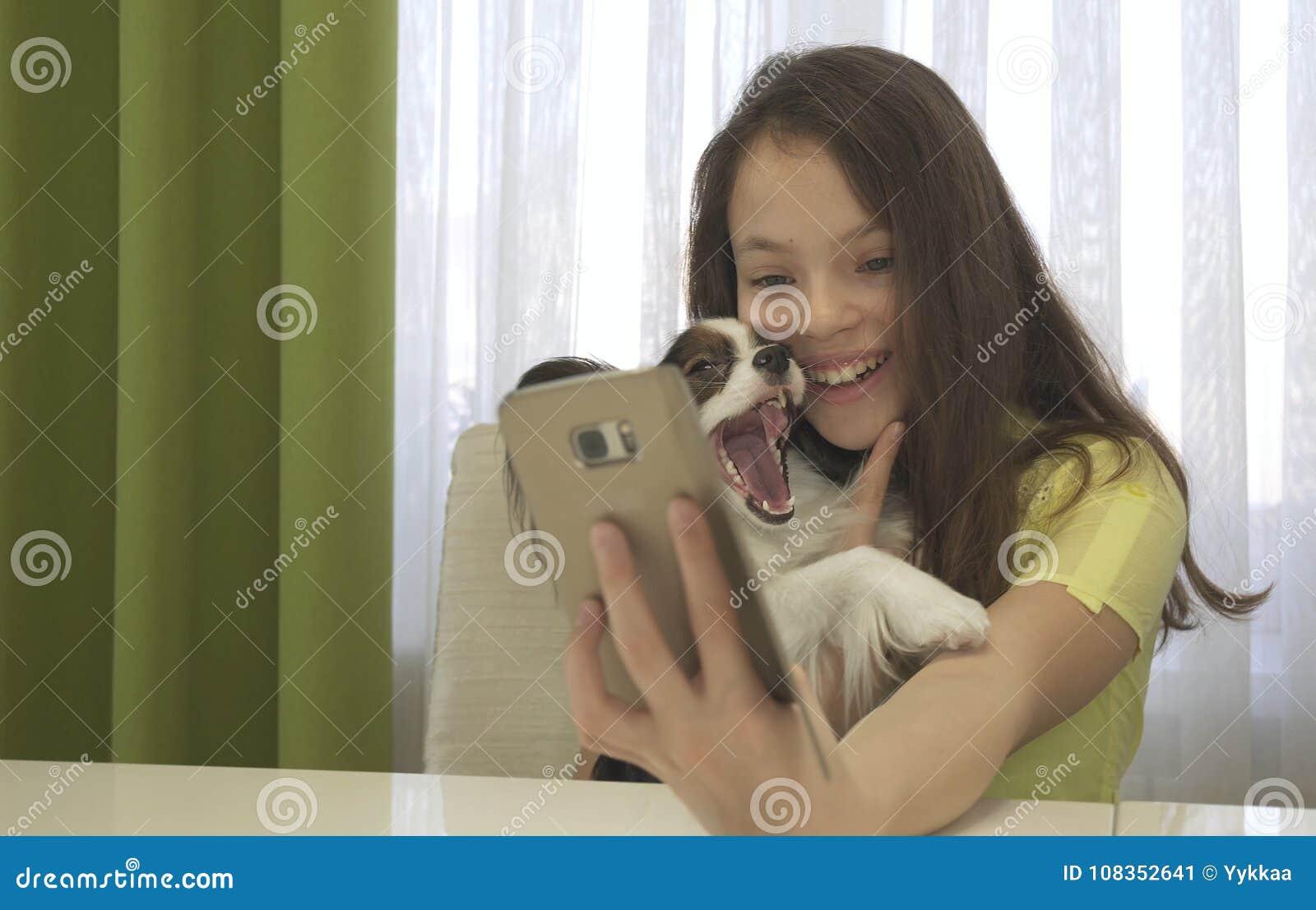 做与她的狗的愉快的十几岁的女孩selfie