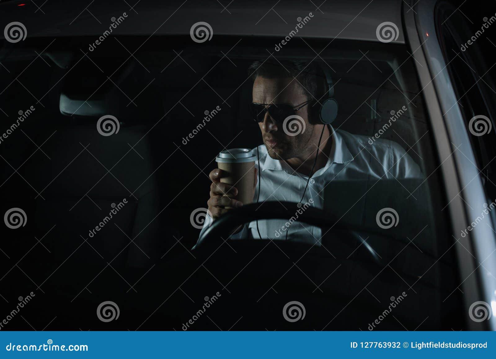 做与膝上型计算机的监视和喝咖啡的耳机的男性私家侦探