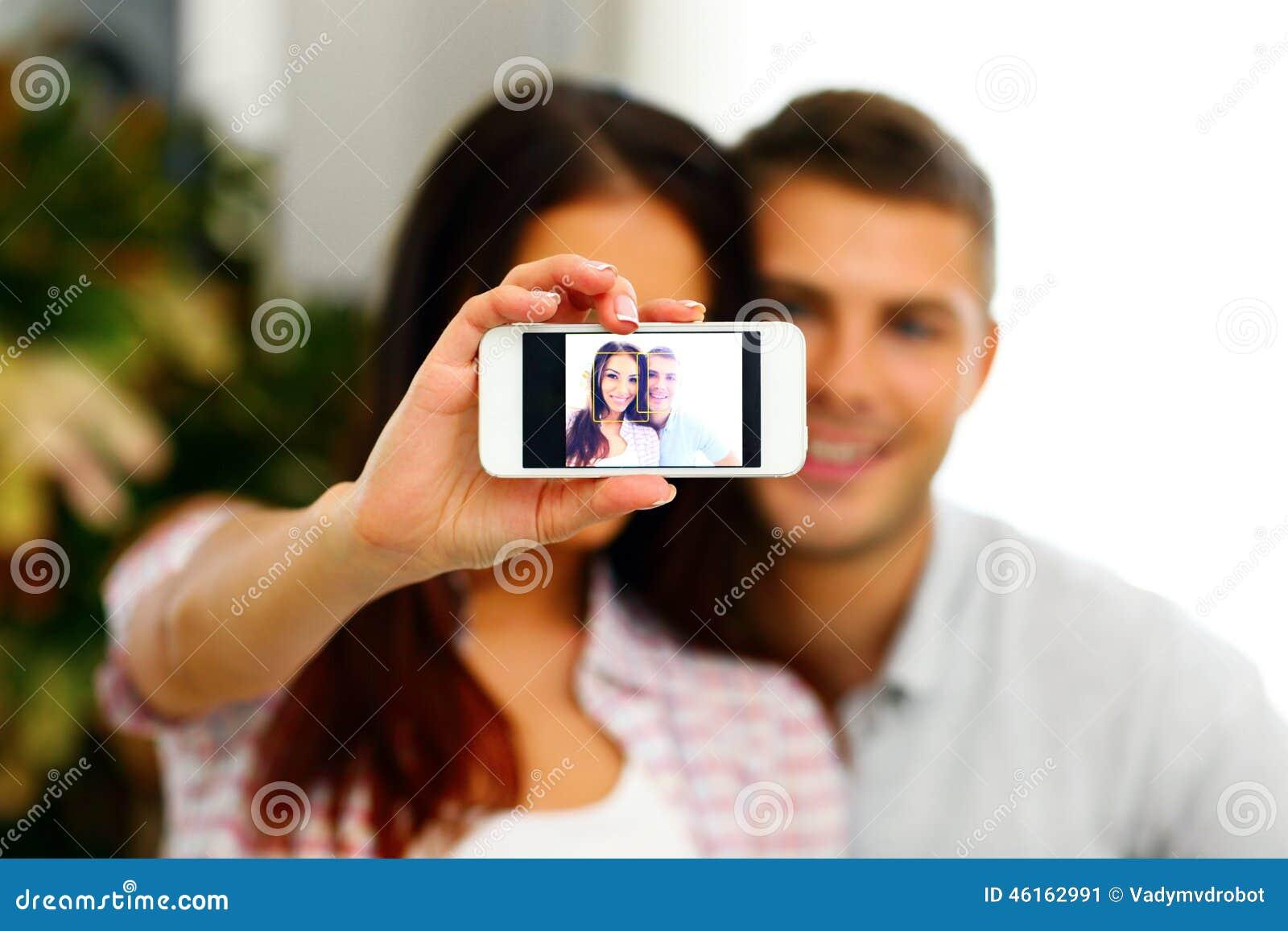 做与smarphone的愉快的夫妇selfie照片