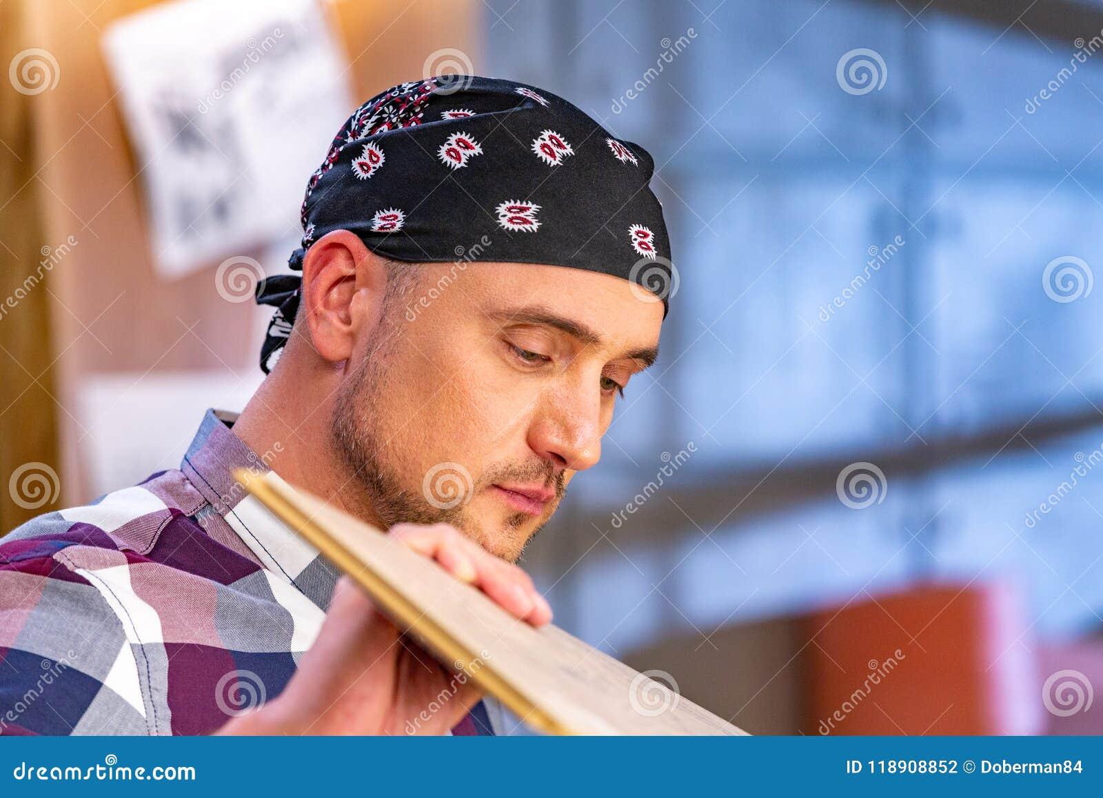 做他的工作的木匠在木匠业车间 木匠业车间测量和裁减层压制品的一个人