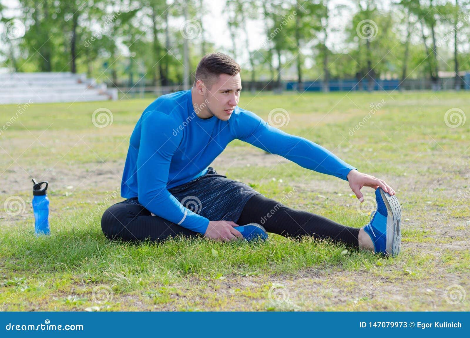 做伸展运动的一位年轻运动员的画象,为早晨训练做准备
