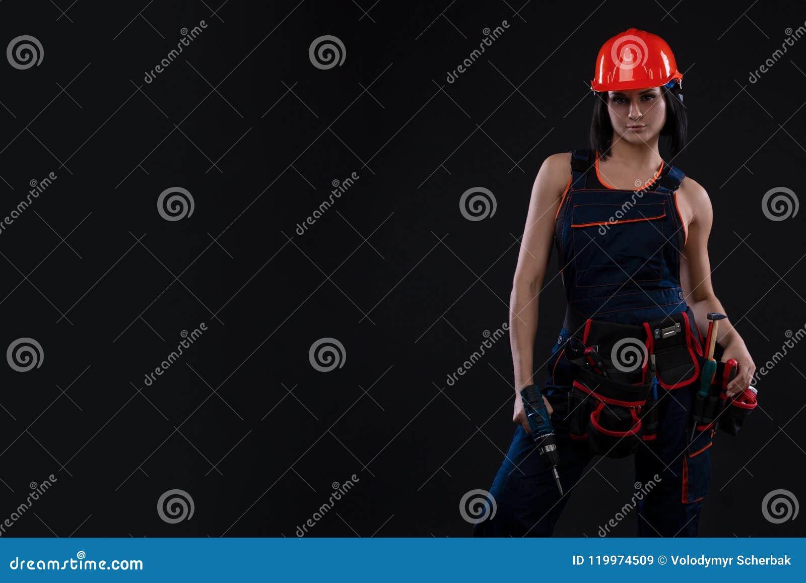 做修理的可爱的少妇在黑背景 一名女性建筑工人的画象 大厦,修理概念 复制