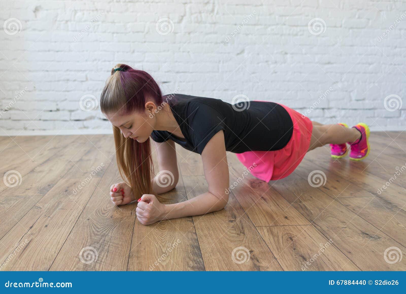 做健身顶楼内部木地板的美丽的女孩