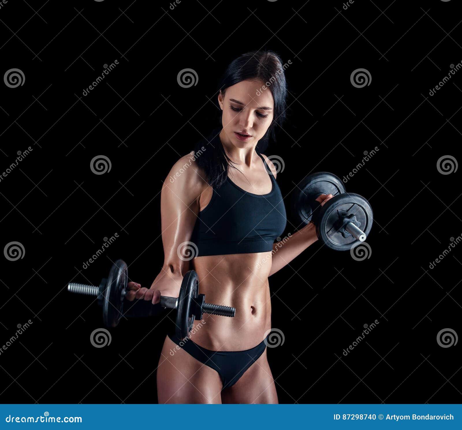 做健身锻炼的运动少妇反对黑背景 加大可爱的健身的女孩干涉与哑铃