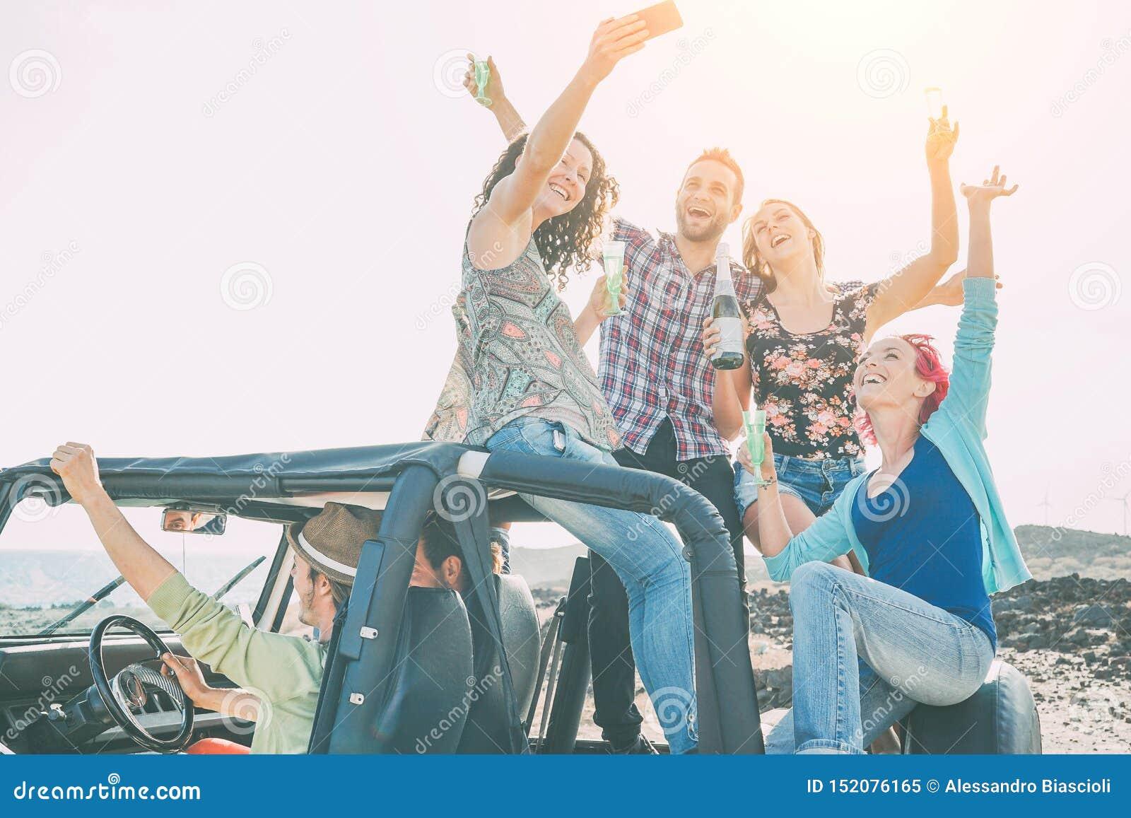 做党的小组愉快的朋友在有吉普车的年轻人乐趣饮用的香槟和照相selfie