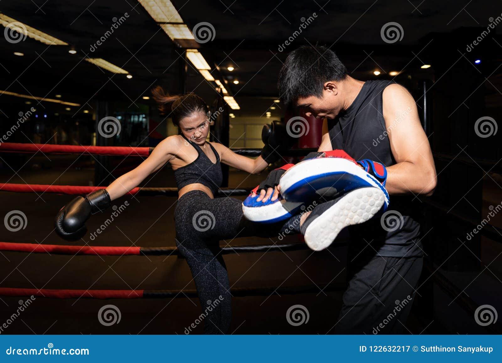做反撞力锻炼的女孩在与个人教练员的kickboxing的训练期间
