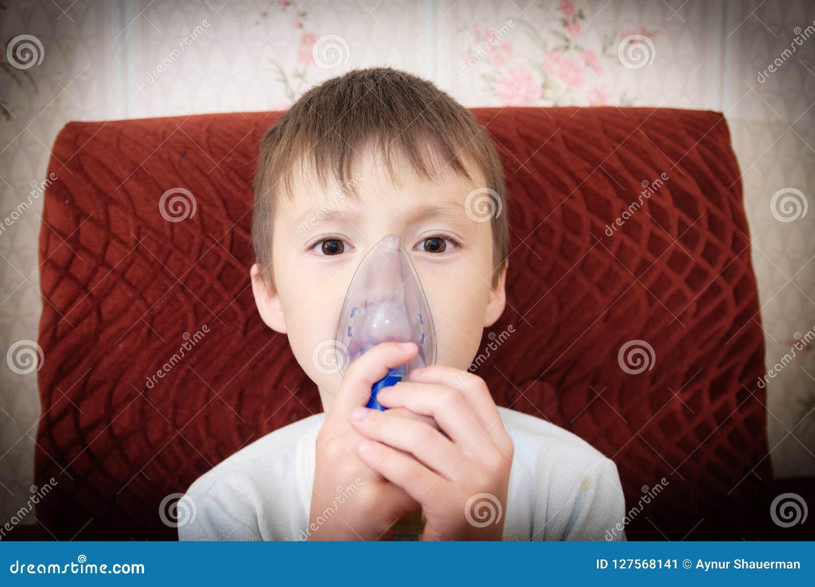 做吸入、呼吸孩子的,吸入器的雾化器面具的病的男孩做法由肺炎或咳嗽