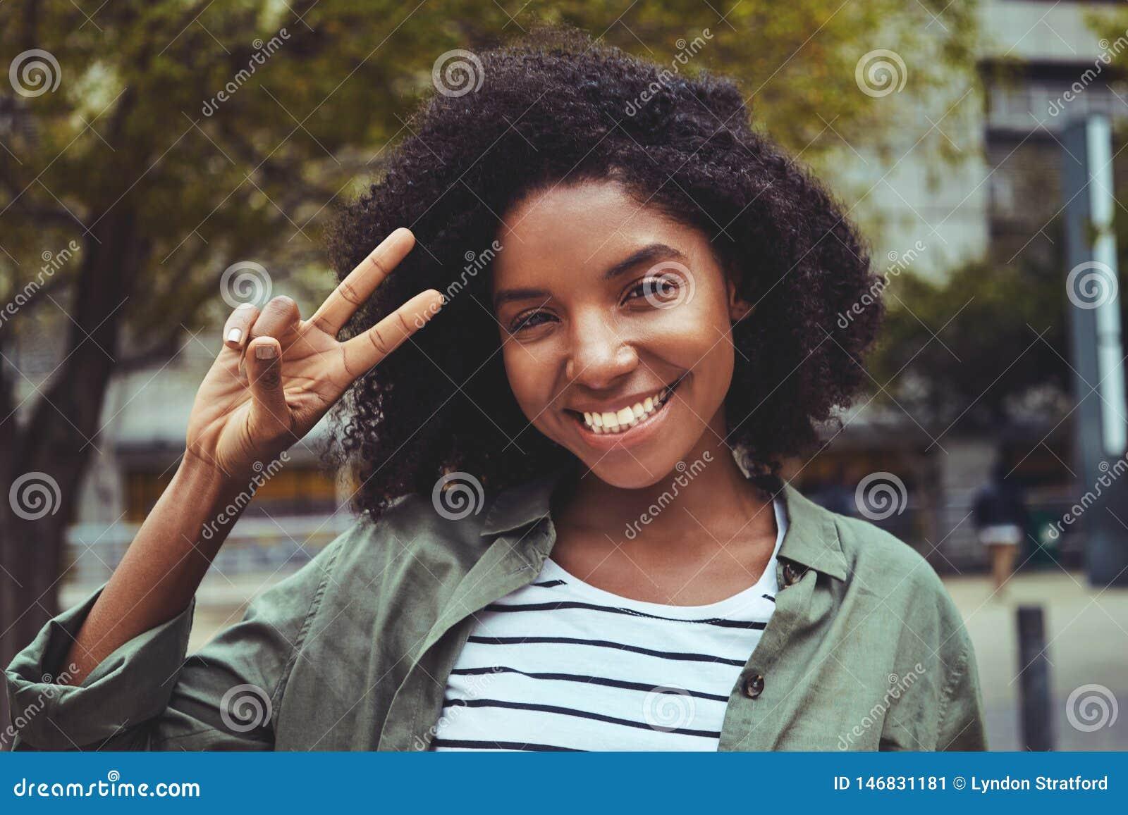 做和平姿态的迷人的年轻女人
