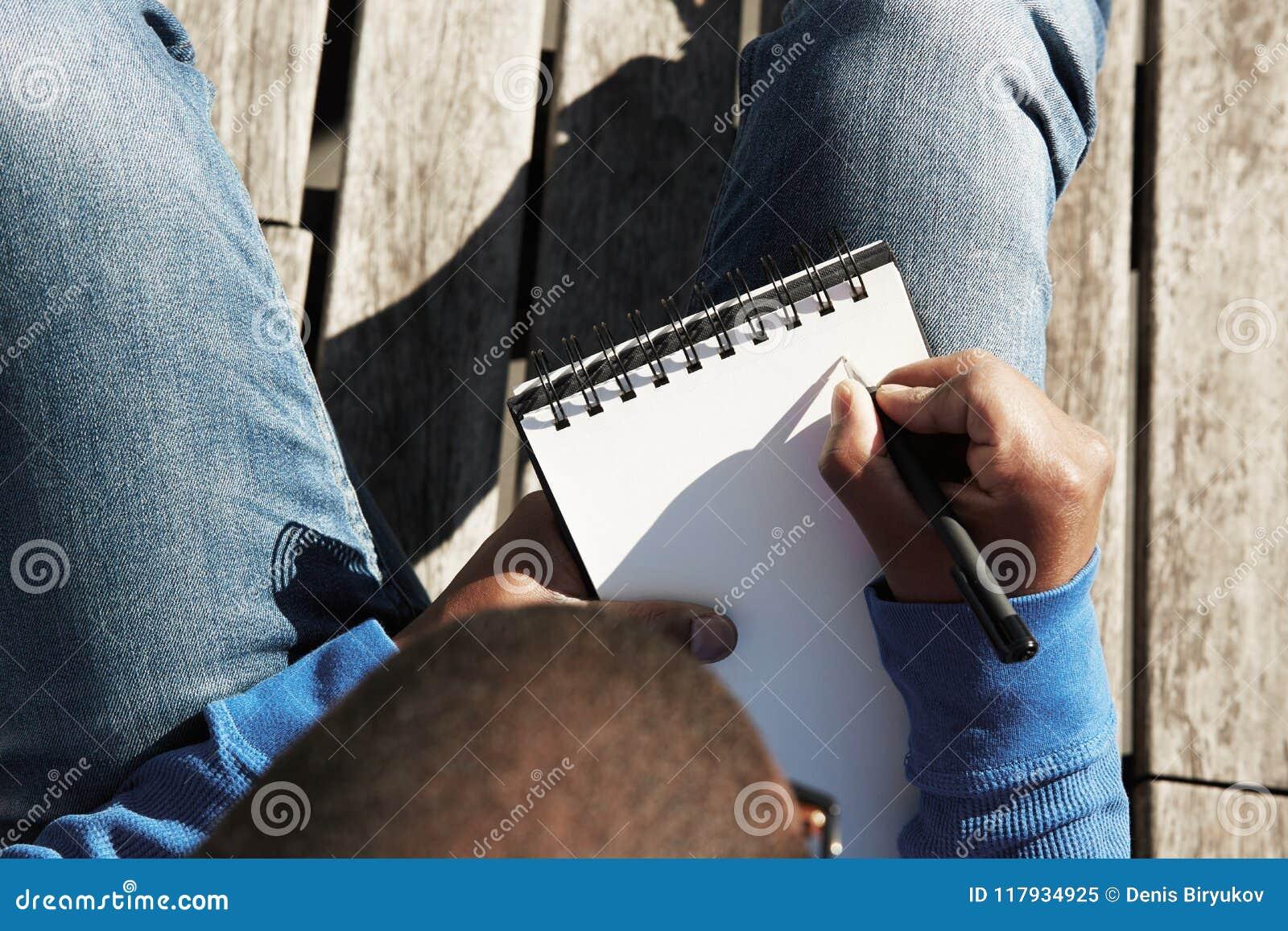 做在习字簿的可爱的随便加工好的年轻黑人男学生笔记,为教训做准备在大学