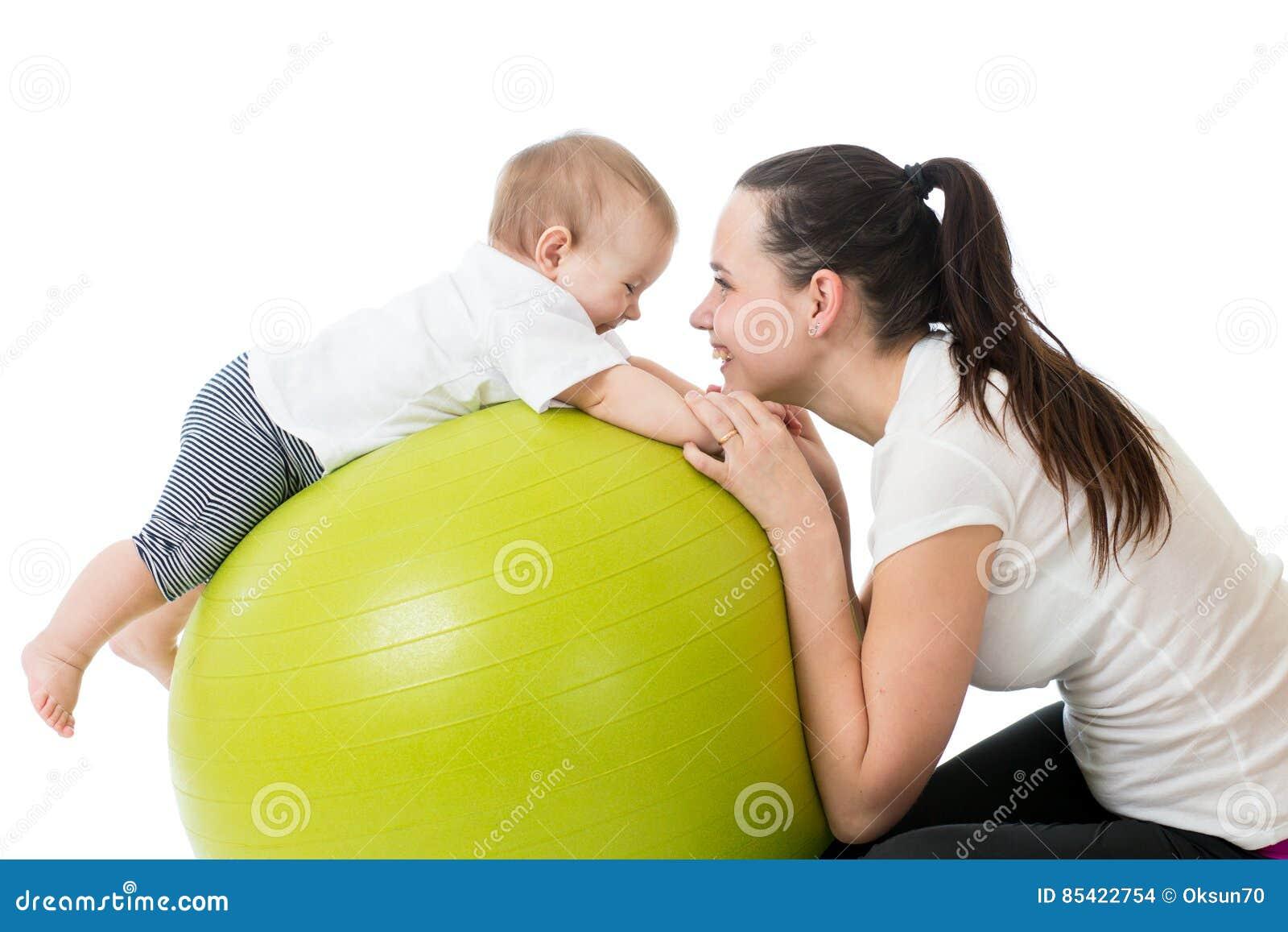年轻做在体操球的母亲和她的婴孩瑜伽锻炼被隔绝在白色