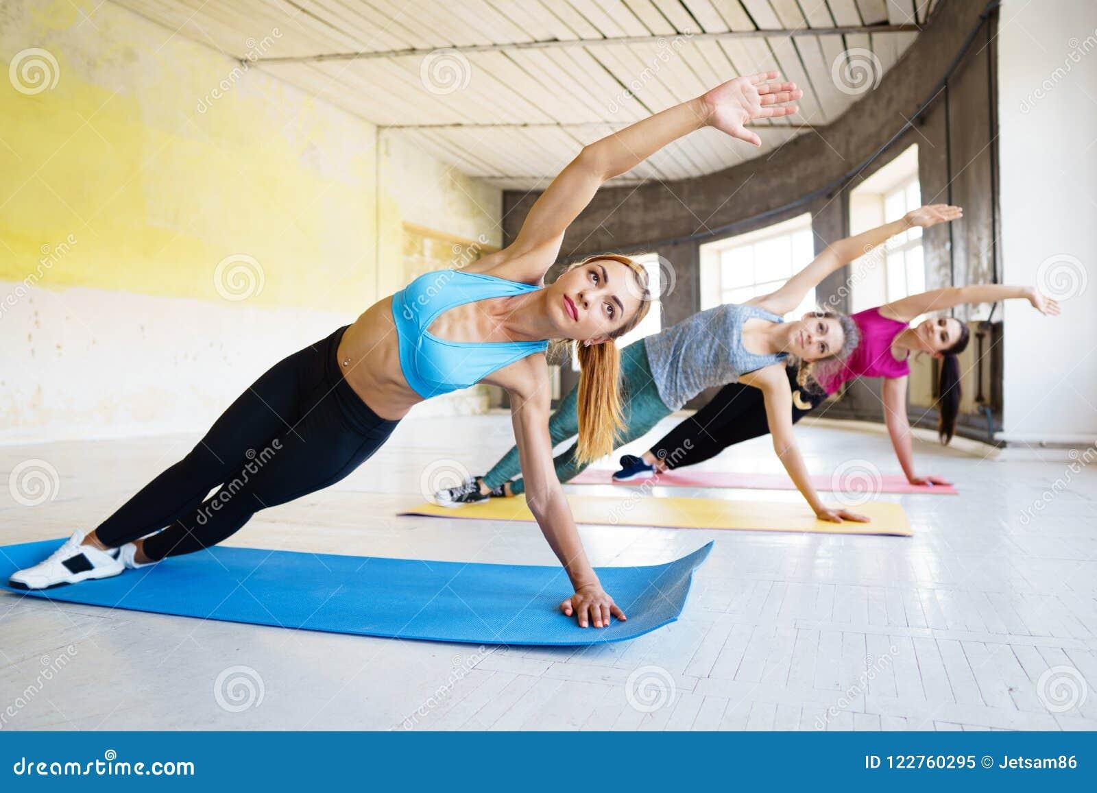 做在健身房的年轻人适合的妇女旁边板条