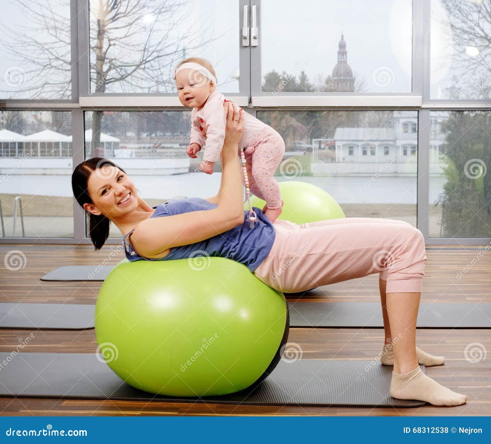 年轻做在地毯的母亲和她的婴孩瑜伽锻炼在健身演播室