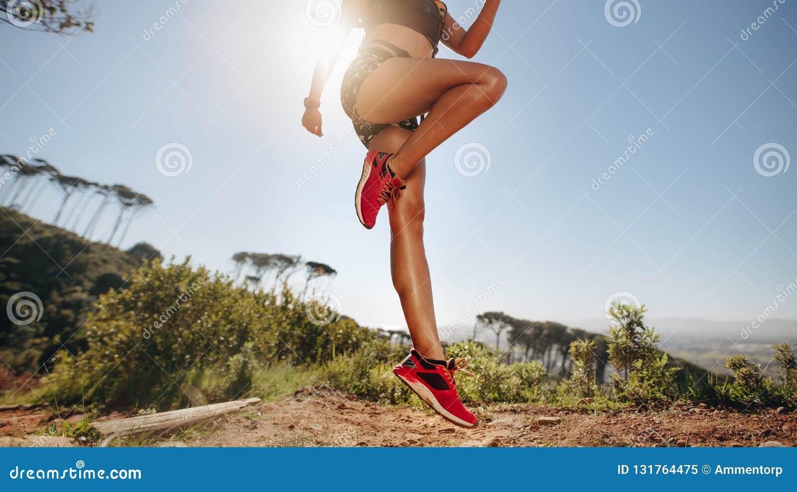 做在小山的女运动员锻炼与太阳在背景中 健身穿戴的使身分兴奋的一名妇女的播种的射击
