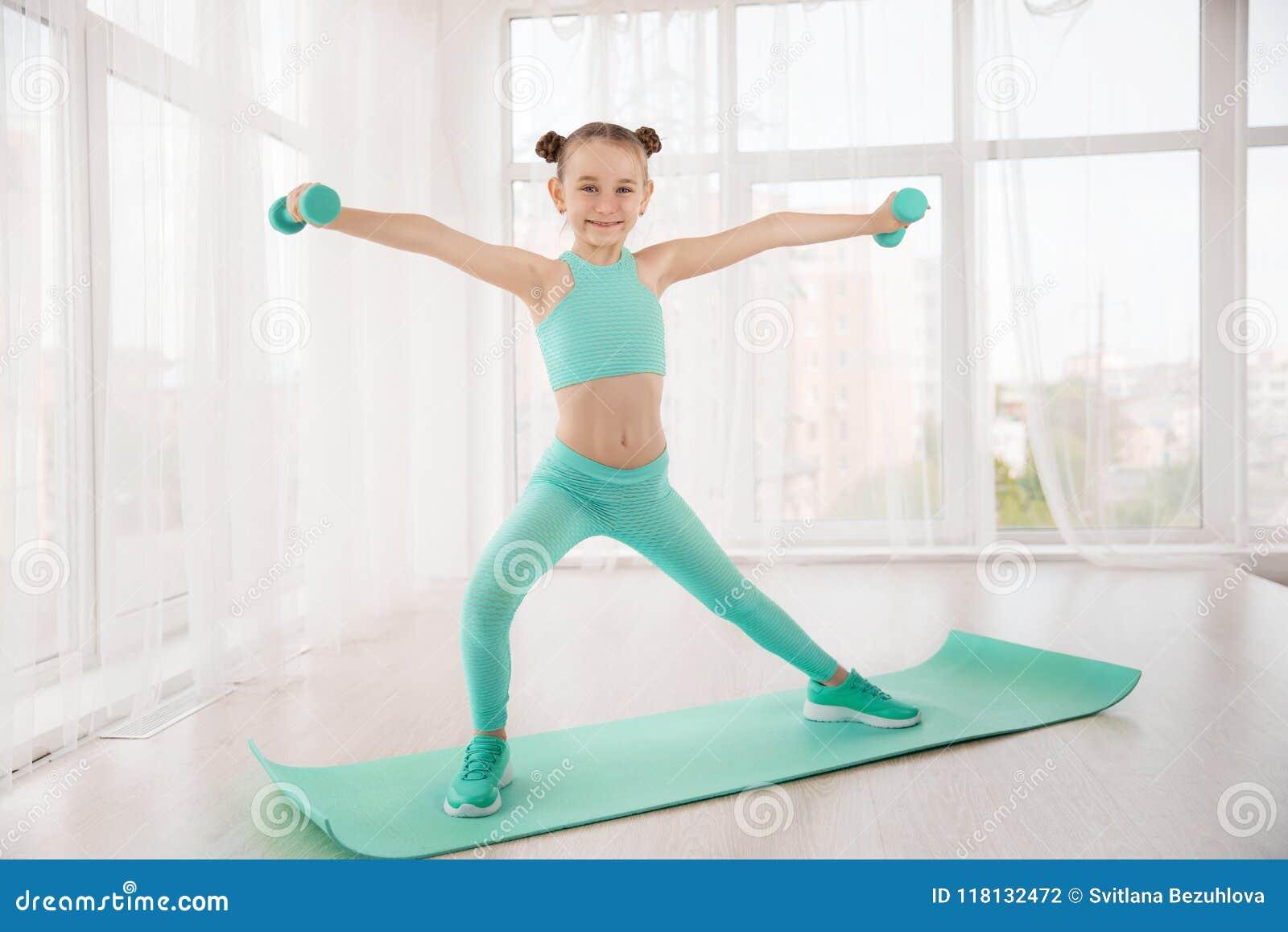 做在席子的运动服的小运动的女孩体操运动员锻炼室内