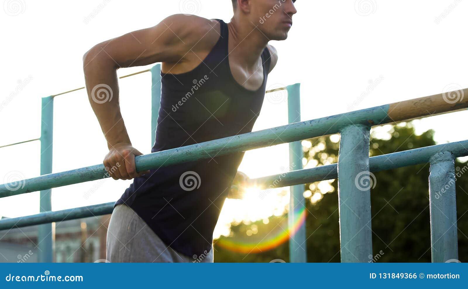 做在平行的标志横线的肌肉年轻男性锻炼户外,体育