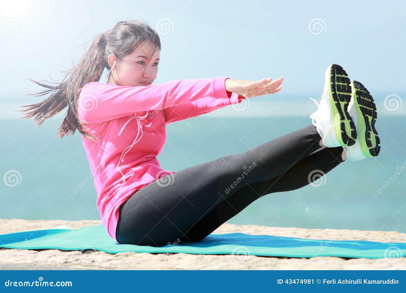 做在海滩的妇女锻炼