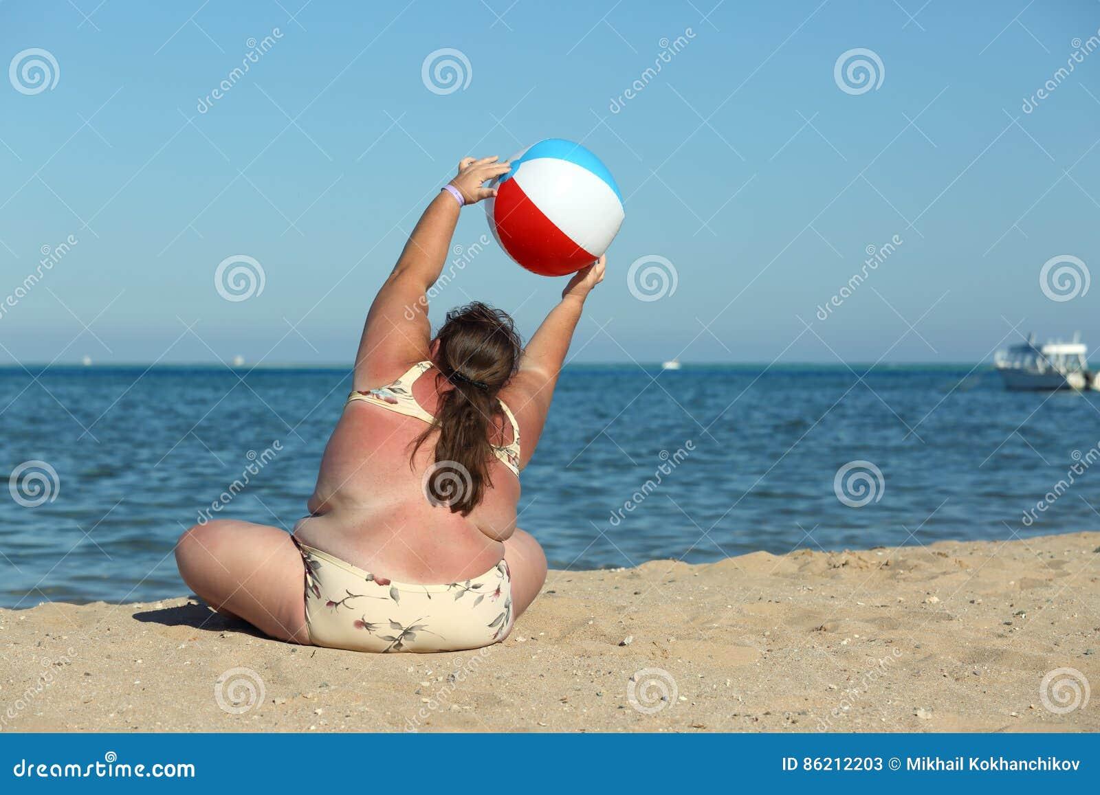 做在海滩的超重妇女体操