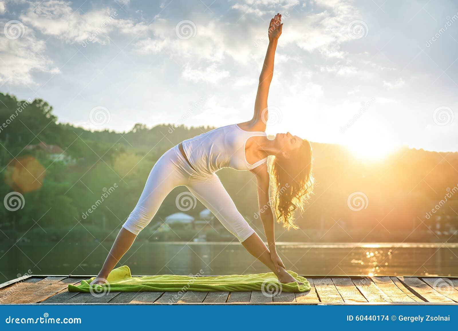 做在湖的妇女瑜伽