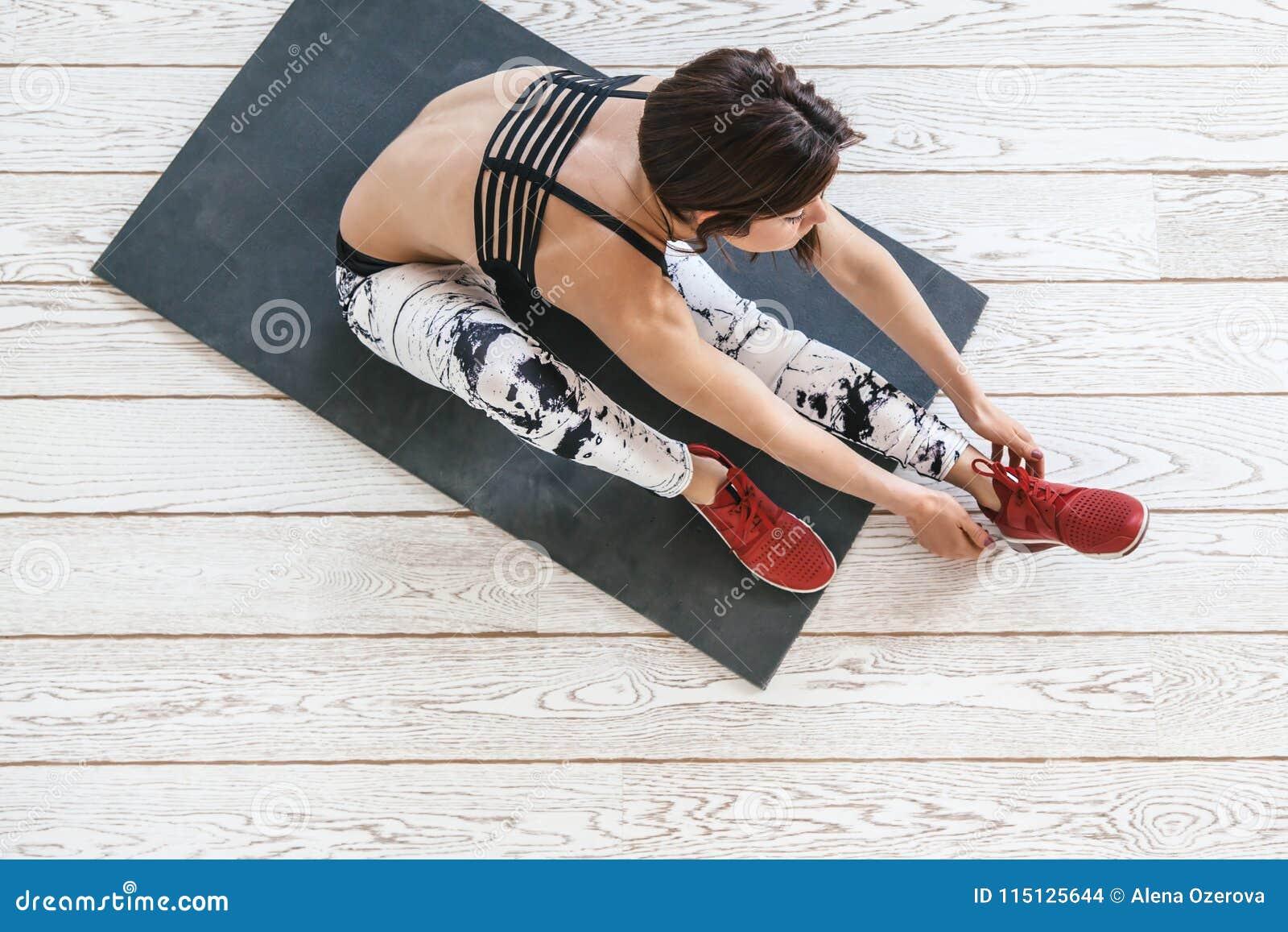 做在白色地板的妇女适合的锻炼