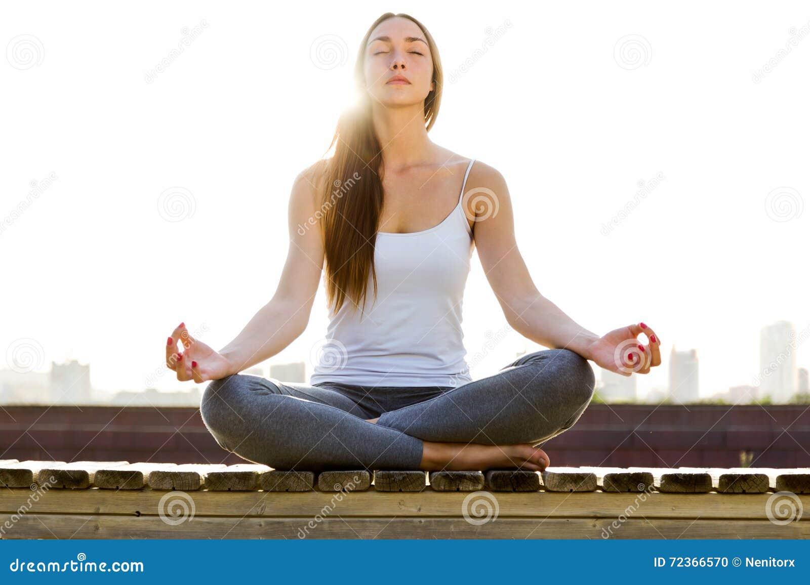 做在街道的美丽的少妇瑜伽
