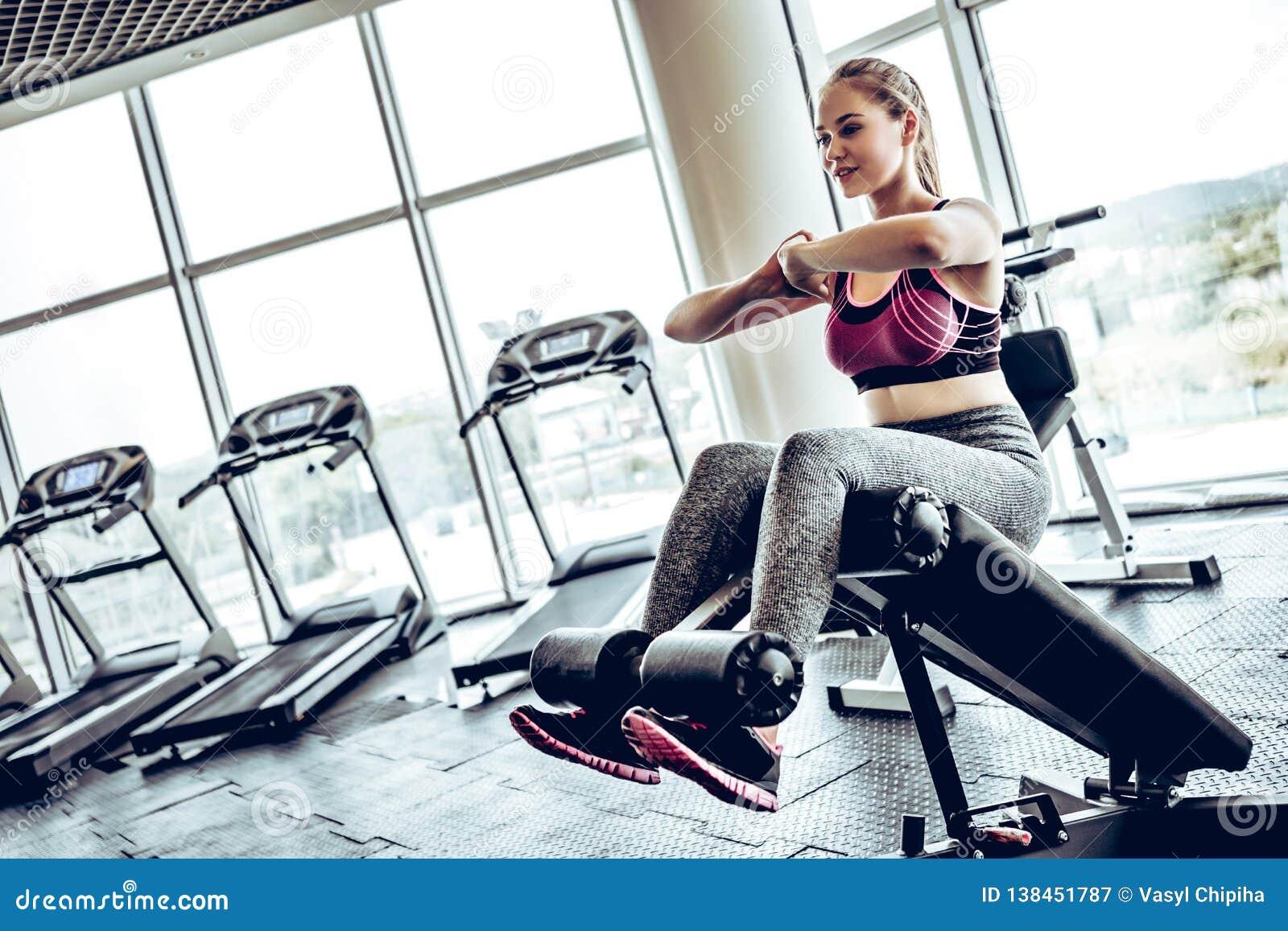 做在长凳的美丽的年轻运动妇女有些咬嚼在健身房