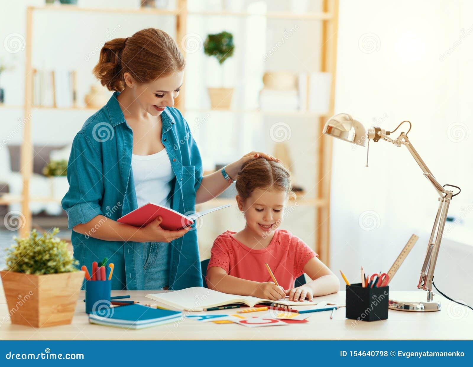 做家庭作业文字和读的母亲和儿童女儿