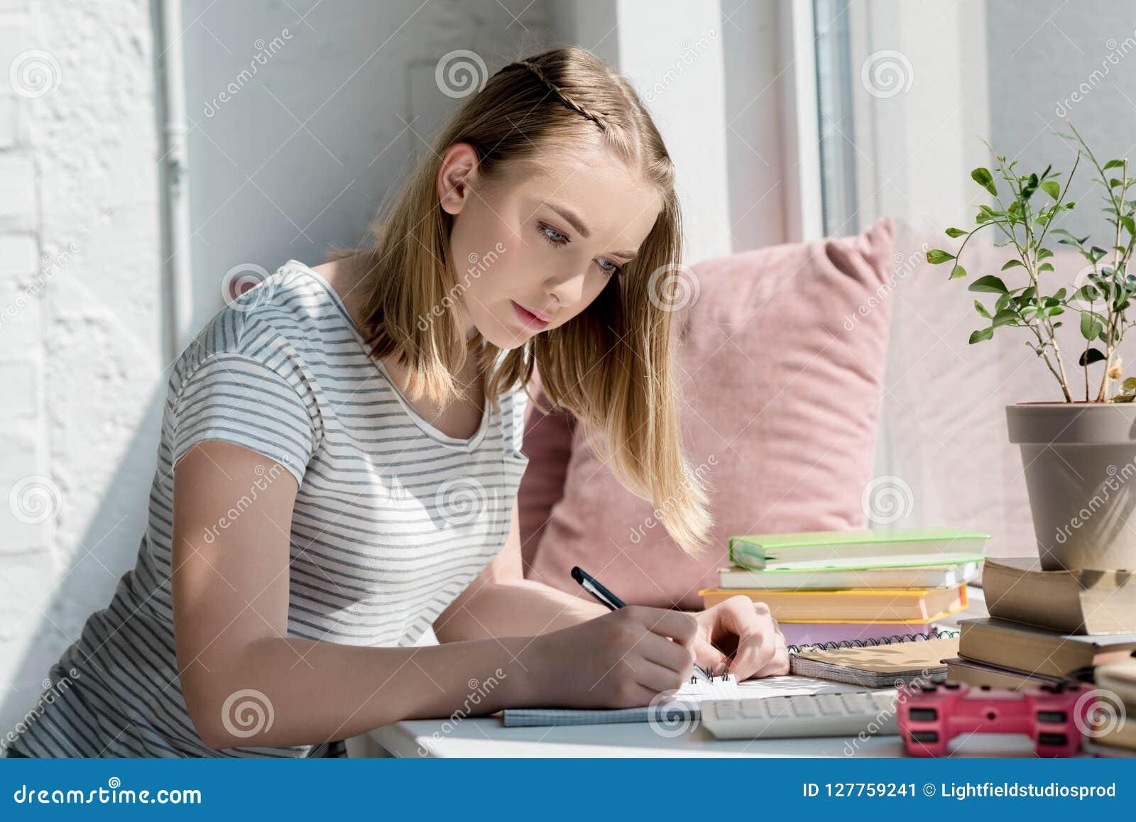 做家庭作业的被聚焦的青少年的学生女孩