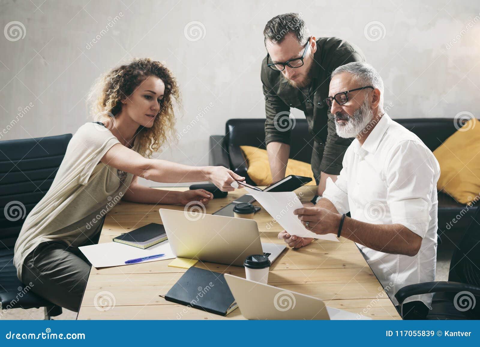 做巨大工作讨论的工友年轻队在现代办公室 有胡子的人谈话与行销经理和