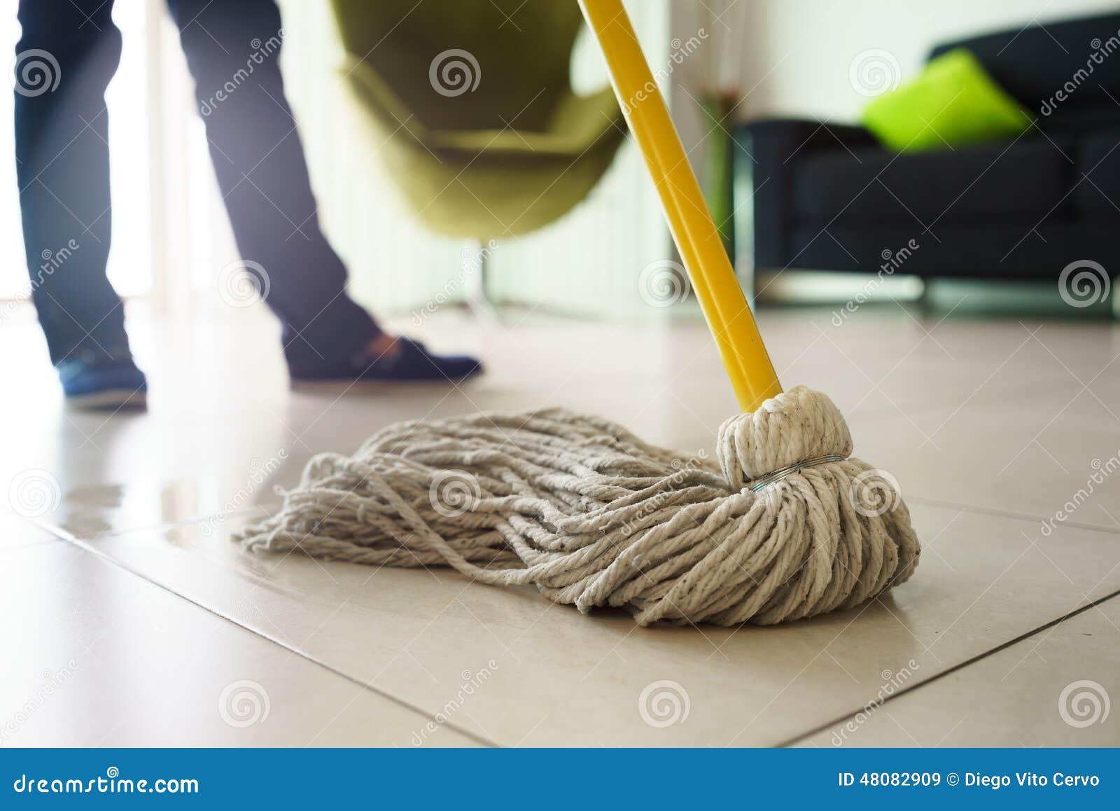 做差事的妇女在家清洗在拖把的地板焦点